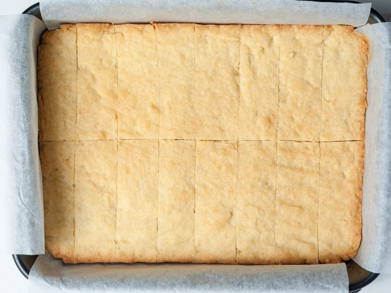 Lemon shortbread in a pan sliced into rectangles