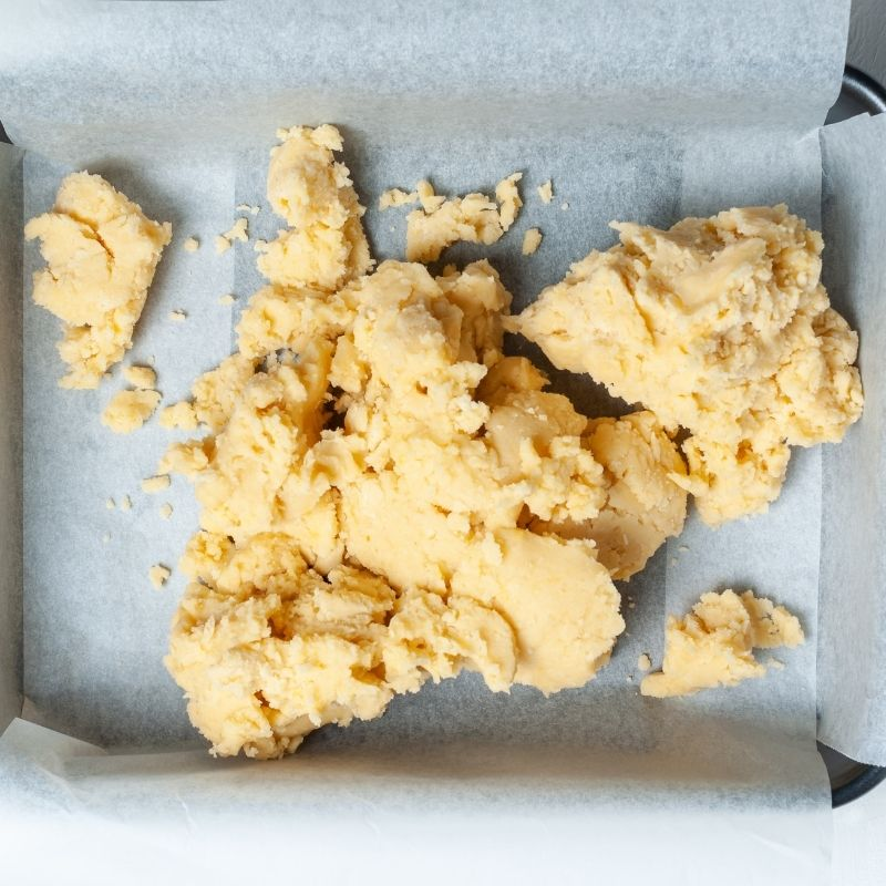 Unbaked dough tipped into a lined baking tray