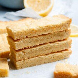 Lemon shortbread slices in a stack beside lemon halves