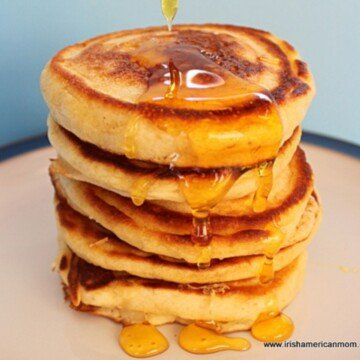 Honey dripping over a stack of golden pancakes