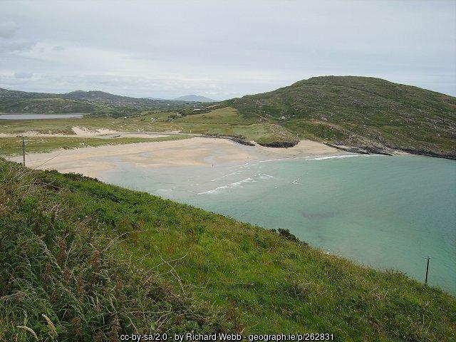 Sandy beach beside green mountain slopes