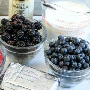Blackberries and blueberries in glass bowls beside cream cheese, cream and vanilla