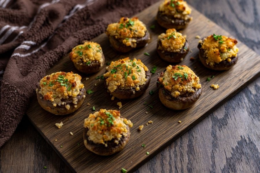 Cheesy stuffed baked stuffed mushrooms on a cutting board