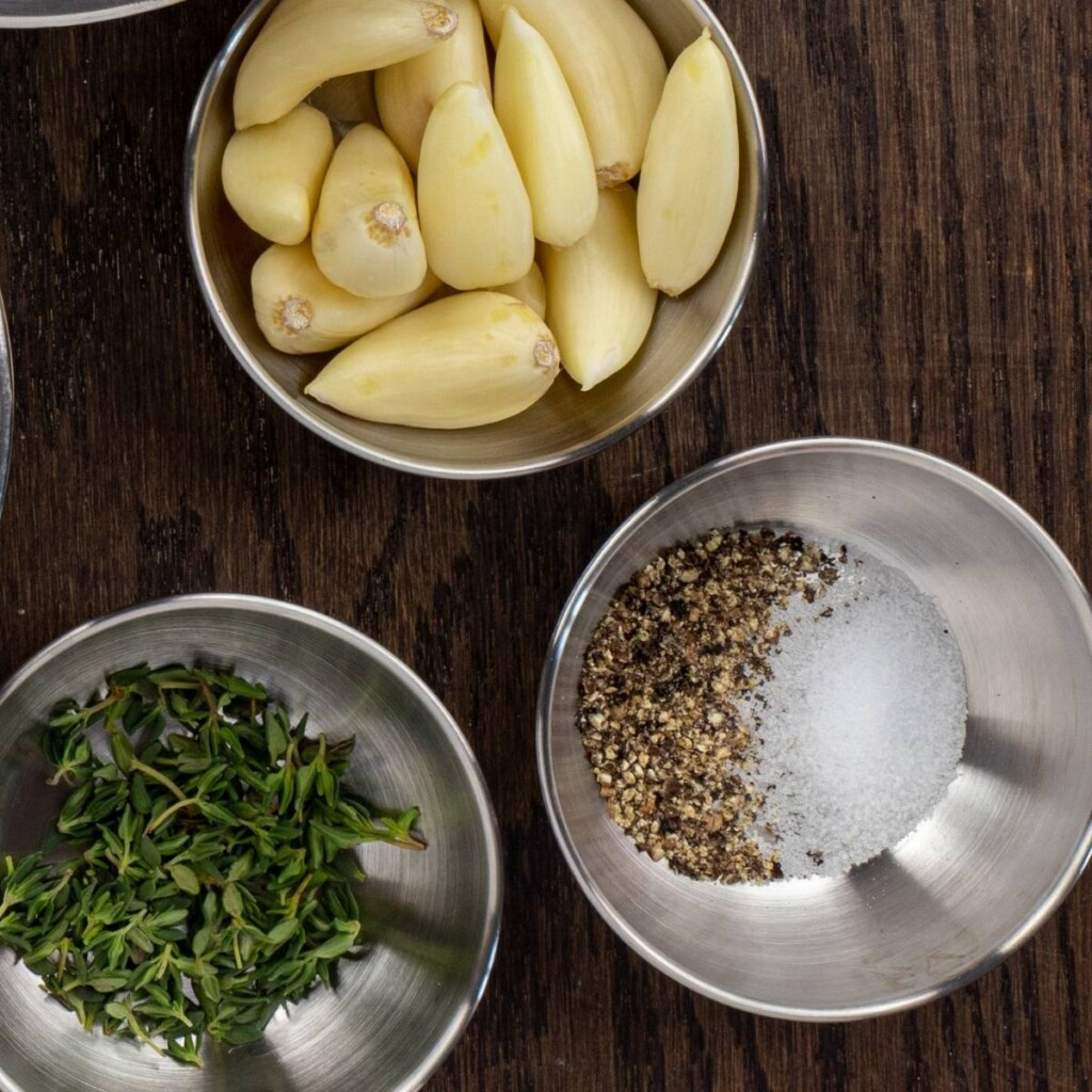Garlic cloves, fresh thyme and salt and pepper in bowls
