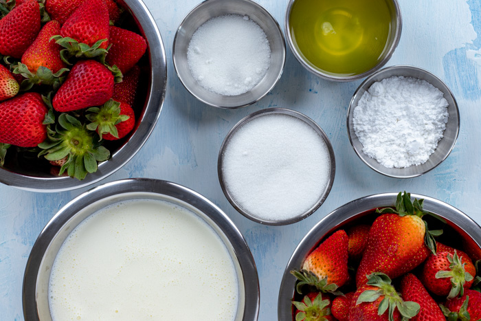 Strawberries, cream and sugars in bowls from an overhead perspective