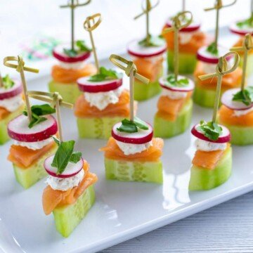 Cucumber, smoked salmon, cream cheese radish and cress appetizer stacks with cocktail sticks on a tray