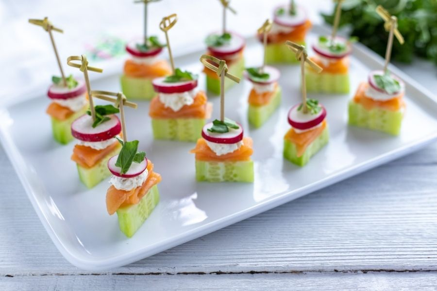 Cucmber, salmon, cream cheese and radish appetizers on a plate