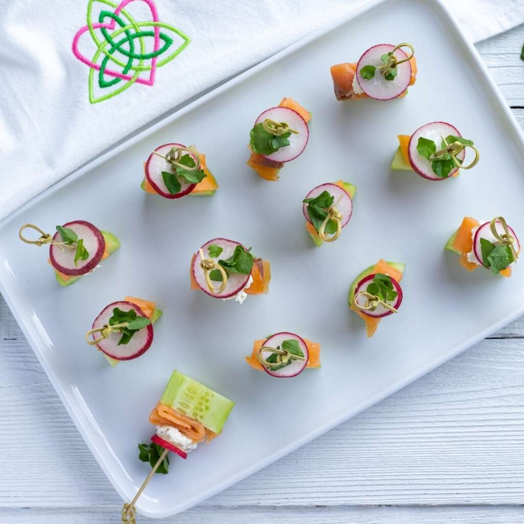 Appetizer bites made with cucumber and salmon on a tray