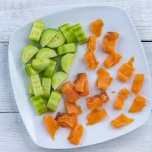 Pieces of cucumber and smoked salmon pieces on a plate