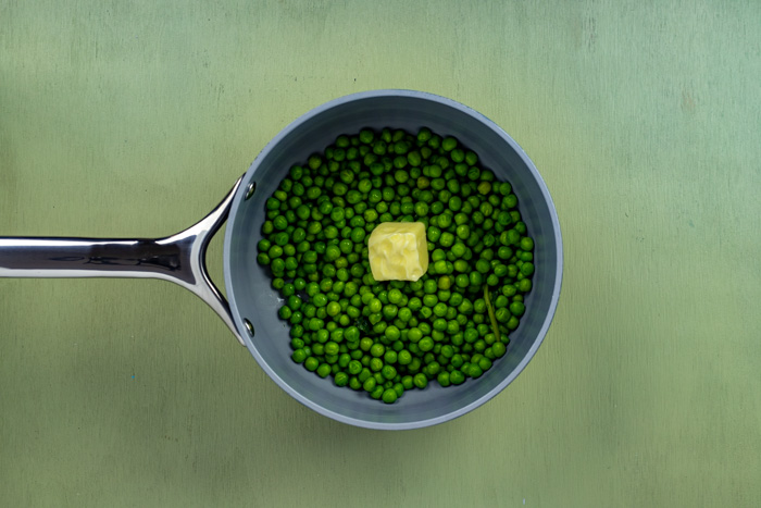 Knob of butter on peas in a saucepan