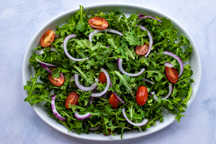 Bed of greens with tomatoes and onions on an oval plate