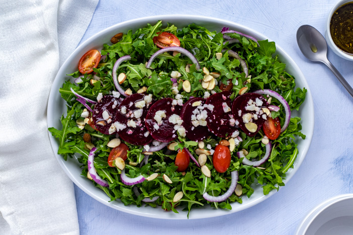 Almonds, cheese crumbles and beets on a bed of green salad leaves