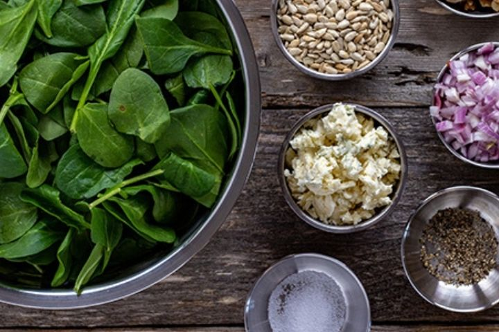 Blue cheese crumbles, spinach leaves, sunflower seeds, diced shallot and salt and pepper in bowls