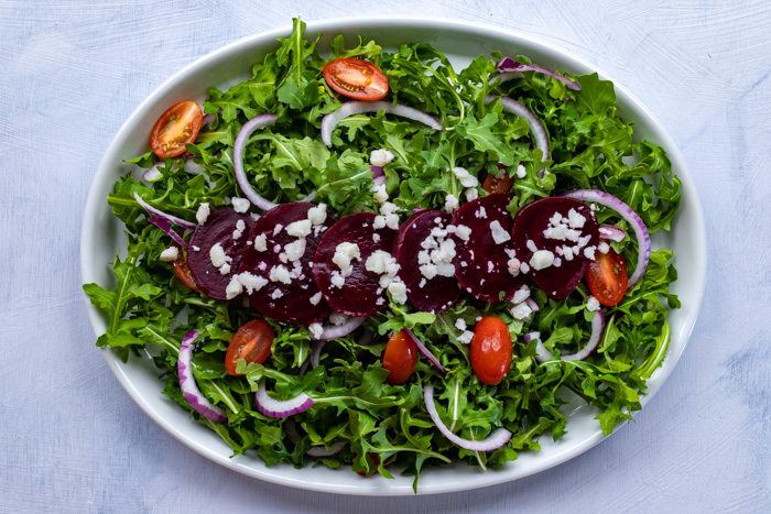 Beetroot and goat cheese salad with cheese crumbles and pickled beet slices on a bed of greens