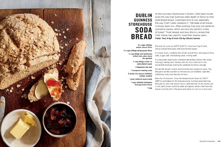 Soda bread with jam and butter on a cutting board beside a text page