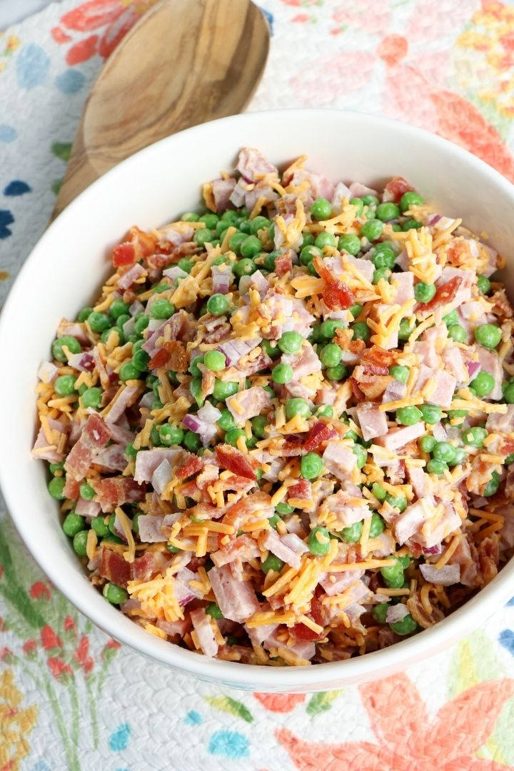 Overhead shot of pea and ham salad in a bowl beside a wooden spoon