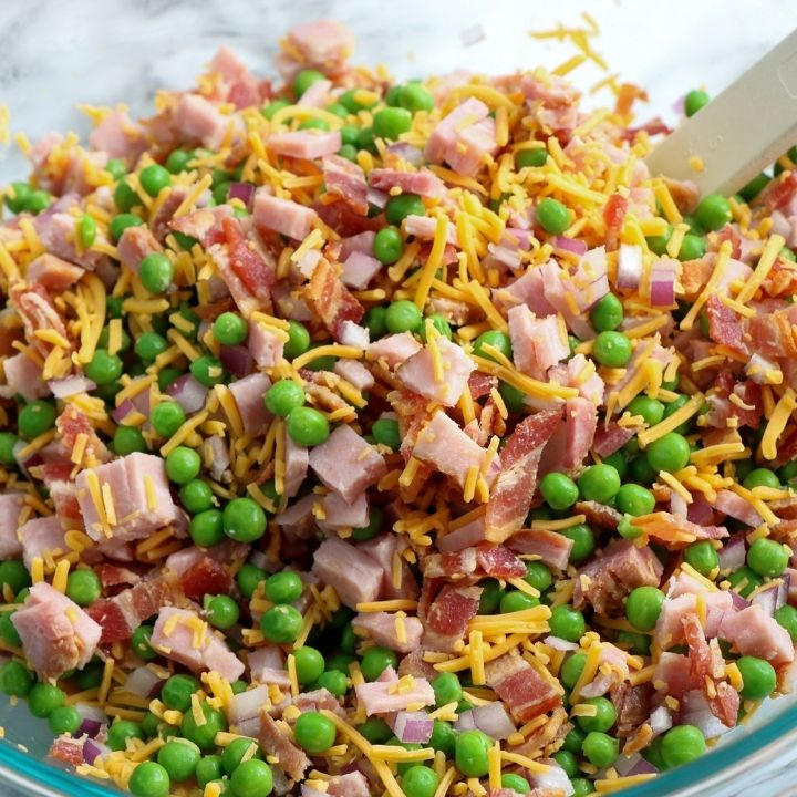 Peas, ham, bacon, onion and shredded cheese mixed together in a bowl