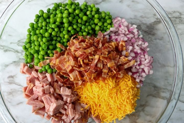 Peas, ham chunks, bacon bits, cheese and chopped onion in a bowl