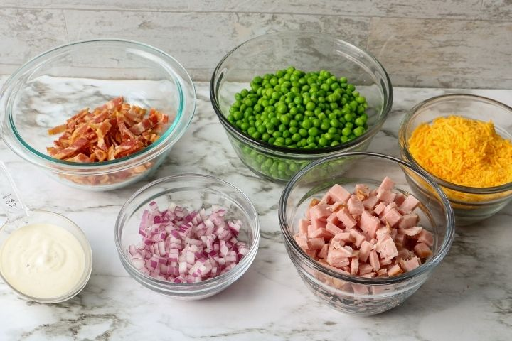Individual bowls of ranch dressing, bacon bits, chopped onion, ham, peas and grated cheese