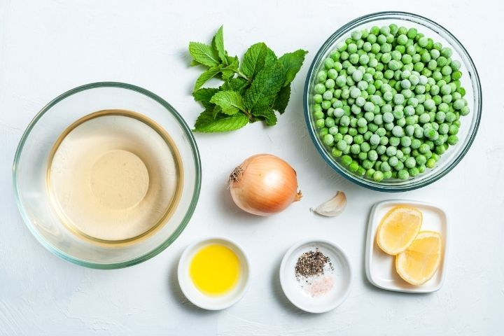 Bowls of pea, stock, butter, salt and papper, lemons slices and and onion and mint sprig