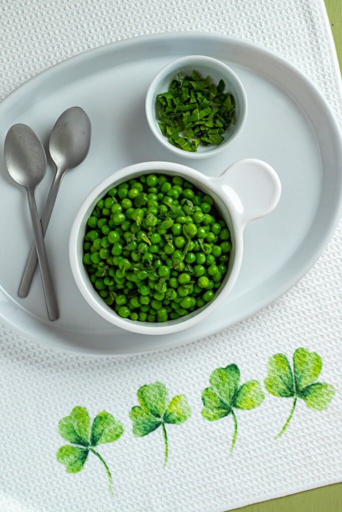 Overhead view of a bowl of peas with mint on a shamrock bordered dish towel