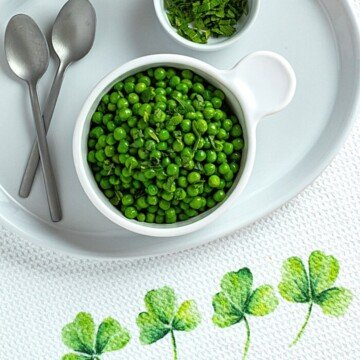 Peas in a bowl beside mint leaves, spoons and a shamrock dish cloth