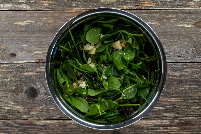 Overhead view of spinach leaves tossed with apples and salad dressing in a bowl