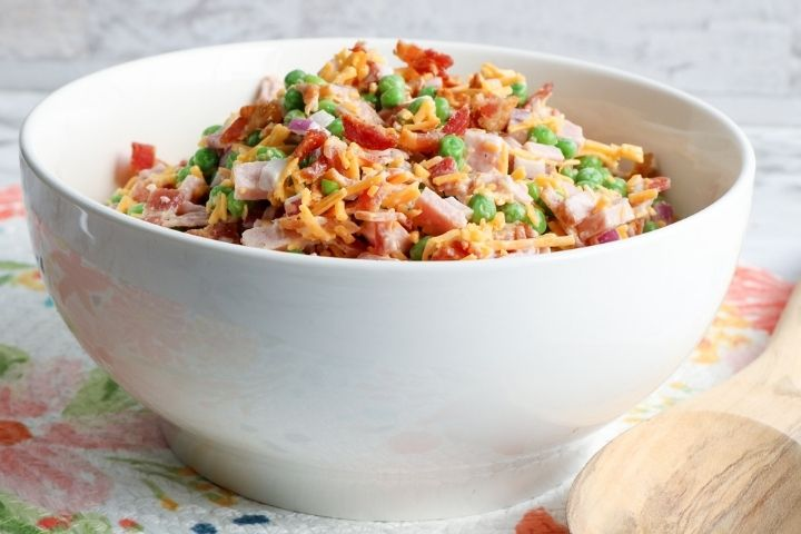 White bowl with a mixed pea, ham and cheese salad
