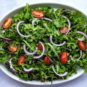 Layered greens, tomatoes and onions on a large platter