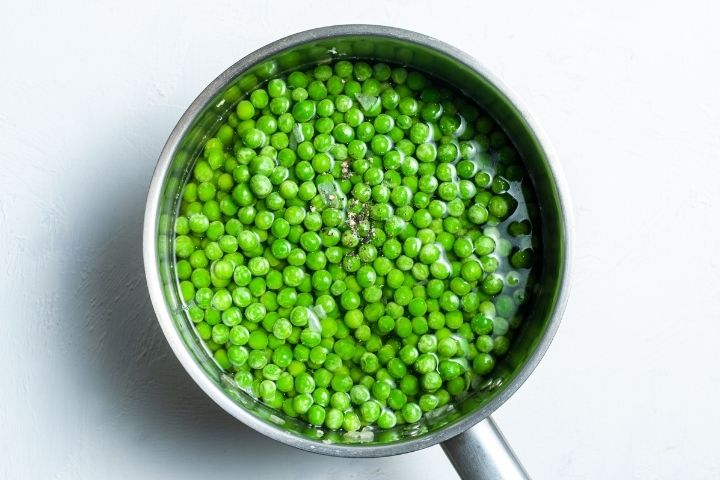 Peas and black pepper in water in a soup pot