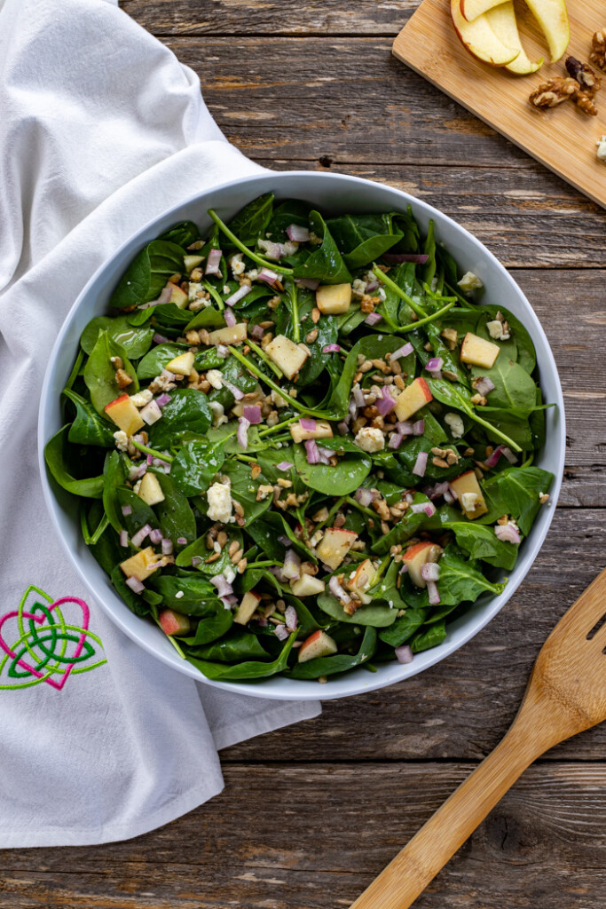 Oveerhead shot of spinach and apple salad in a bowl with a dish cloth and wooden fork