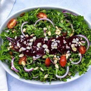 Almonds, beetroot, cheese crumbles on a bed of greens on a platter