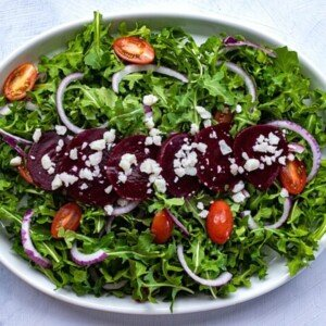 Sliced beetroot and crumbled cheese on a bed of greens