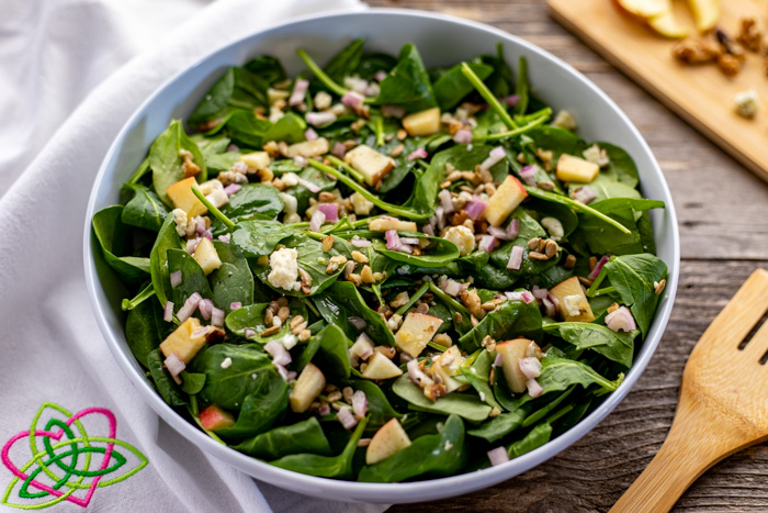 Bowl of spinach, apple, blue cheese and nut salad