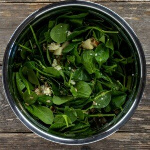 Spinach leaves in a bowl with apple pieces