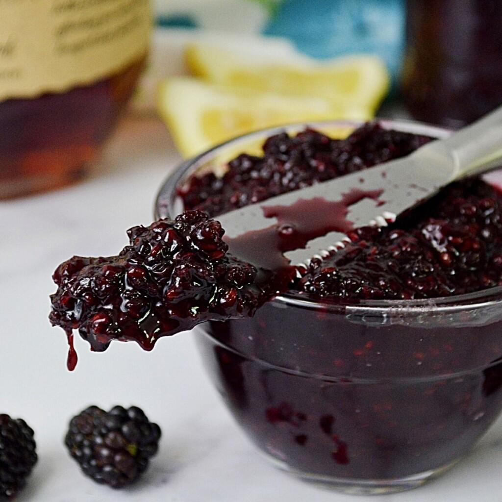 Blackberry jam on a knife on a bowl of jam