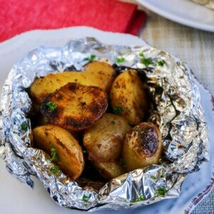 Potatoes in a foil packet on a white plate