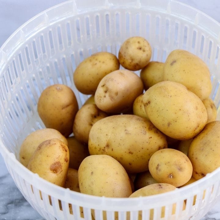 Plastic collander of washed potatoes