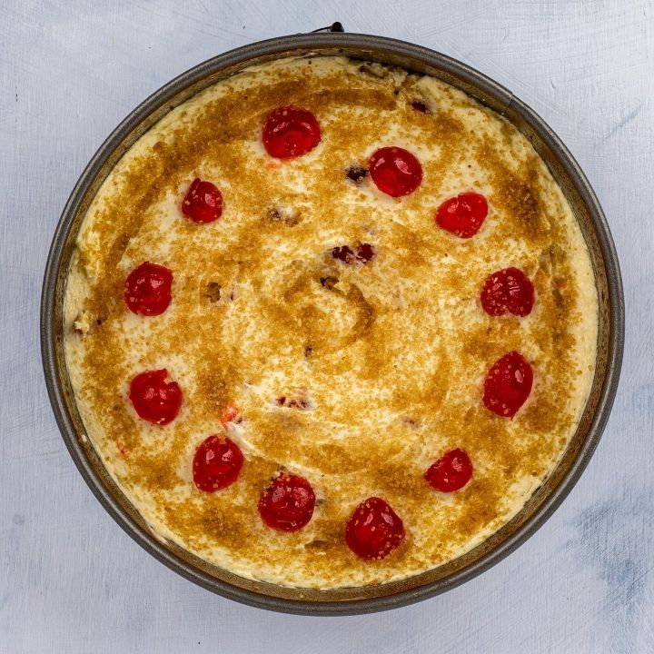 Circle of cherries on top of cake batter in a baking pan
