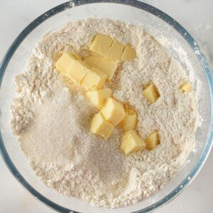 Cubes of butter in a bowl of flour and sugar