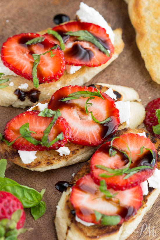 Bread slices topped with cheese and sliced strawberries